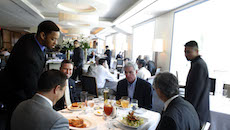 A waiter serves lunch entrees to patrons at Charlie Palmer S