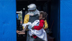 Dr. Steven Hatch carries Blessing Gea, 9, from the suspected ward to the confirmed high-risk ward after a blood test showed her positive for Ebola, at a clinic run by the International Medical Corps.