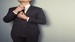 A young businessman is adjusting his tie